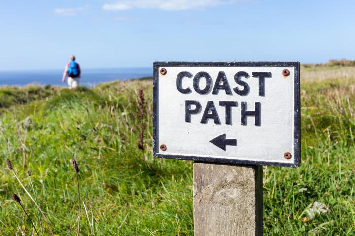 an_old_coast_path_sign_on_the_cornish_cliffs_near_tintagel_uk___selective_focus_on_the_sign_with_a_female_walker_out_of_focus_in_the_background